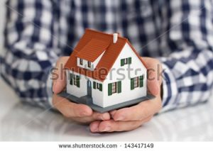 stock-photo-hand-over-mini-house-with-depth-of-field-143417149
